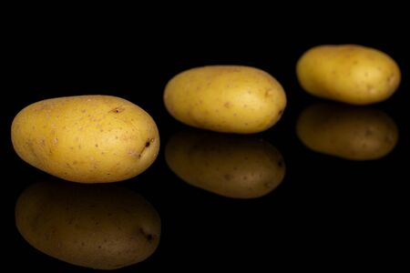 Group of three whole pale yellow potato placed diagonally isolated on black glass