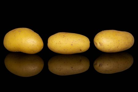 Group of three whole pale yellow potato in row isolated on black glass
