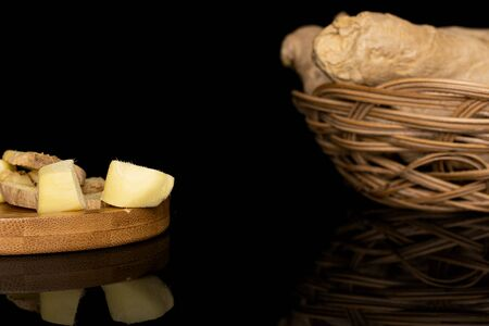 Group of lot of whole three slices two pieces of fresh brown ginger in round rattan bowl on round bamboo coaster isolated on black glass Stock Photo
