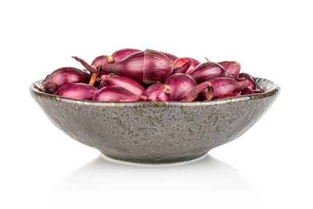 Lot of whole small red onion bulb in dark ceramic bowl isolated on white background