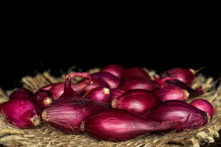Lot of whole small red onion bulb on natural sackcloth isolated on black glass Reklamní fotografie