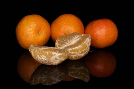 Group of three whole one half one piece of fresh orange mandarin isolated on black glass
