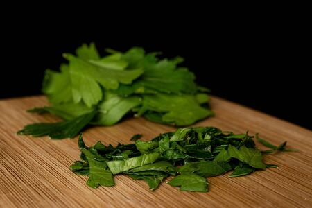 Lot of whole lot of pieces of fresh green parsley on bamboo cutting board isolated on black glass Banco de Imagens