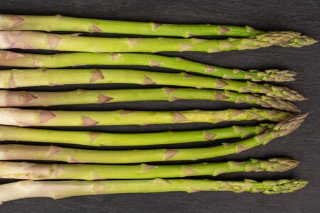 Lot of whole healthy green asparagus flatlay on grey stone