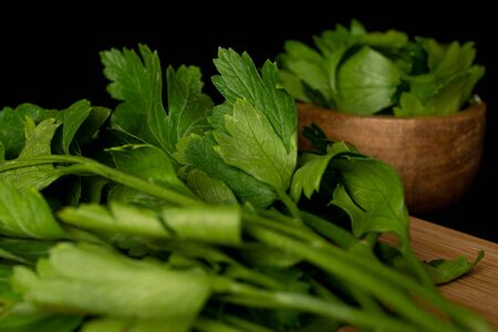 Lot of whole lot of pieces of fresh green parsley in bamboo bowl on bamboo cutting board isolated on black glass
