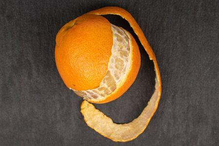 One whole fresh orange mandarin flatlay on grey stone