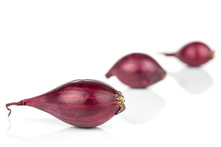 Group of three whole small red onion bulb placed diagonally isolated on white background