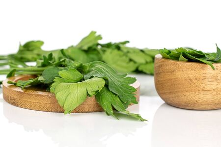 Lot of whole lot of pieces of fresh green parsley on round bamboo coaster in bamboo bowl isolated on white background