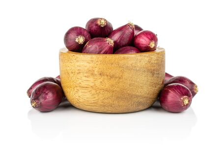 Lot of whole small red onion bulb in tiny wooden bowl isolated on white background
