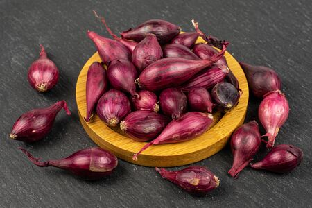Lot of whole small red onion bulb on bamboo coaster on grey stone Reklamní fotografie