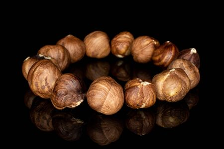 Lot of whole tasty brown hazelnut circle isolated on black glass