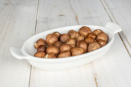 Lot of whole tasty brown hazelnut on white ceramic plate on white wood