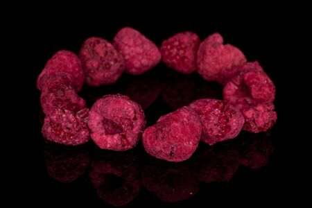 Lot of whole dried raspberry circle isolated on black glass Reklamní fotografie