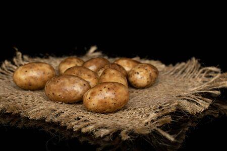 Lot of whole tiramisu brown almond nut with jute fabric isolated on black glass Reklamní fotografie - 136233751
