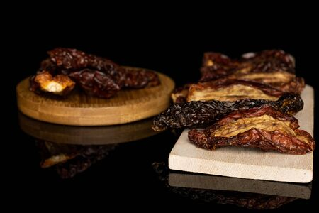 Lot of whole dried red tomato piece on wooden cutting board on round bamboo coaster isolated on black glass