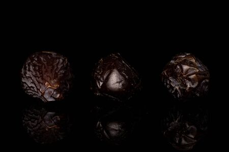Group of three whole dried brown date fruit isolated on black glass Reklamní fotografie - 136233778