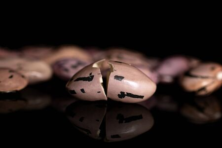 Group of lot of whole two halves of fresh speckled bean pinto isolated on black glass Stok Fotoğraf