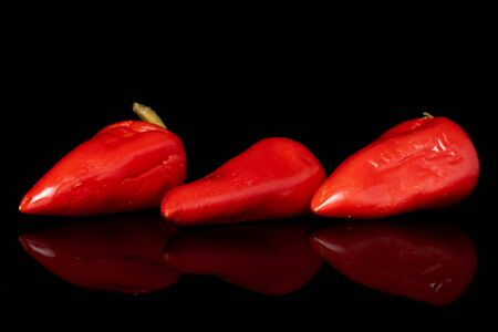 Group of three whole pickled red pepper isolated on black glass