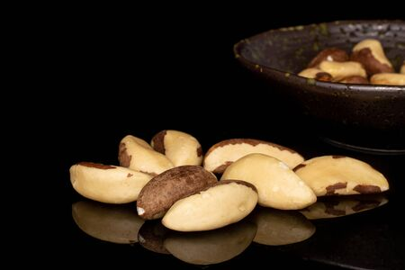 Lot of whole unshelled brazil brown nut in glazed bowl isolated on black glass Reklamní fotografie