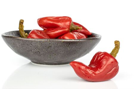 Lot of whole pickled red pepper in glazed bowl isolated on white background Stock Photo
