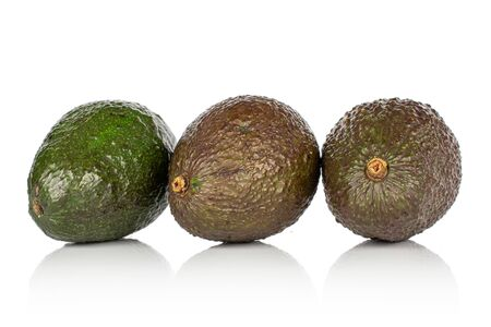 Group of three whole fresh green avocado isolated on white background