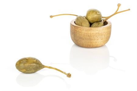 Lot of whole pickled green caper in bamboo bowl isolated on white background