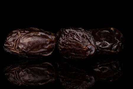 Group of three whole dried brown date fruit isolated on black glass