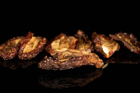 Group of seven whole dried red tomato piece isolated on black glass
