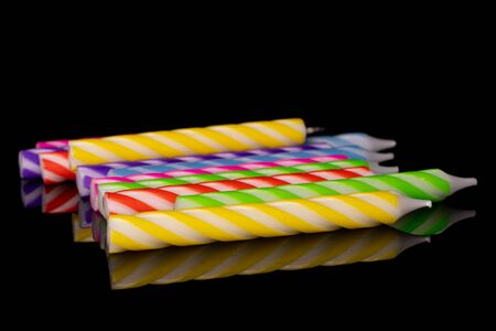 Lot of whole bright birthday cake candle isolated on black glass