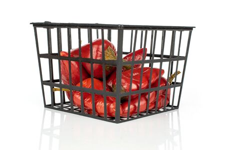 Lot of whole pickled red pepper with  black plastic basket isolated on white background