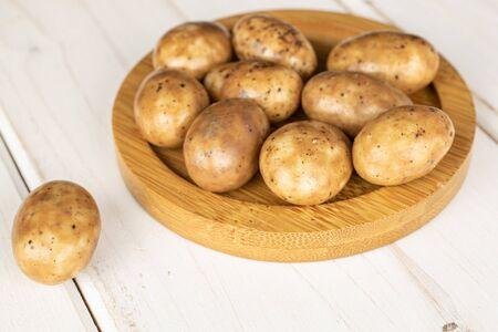 Lot of whole tiramisu brown almond nut on round bamboo coaster on white wood Reklamní fotografie