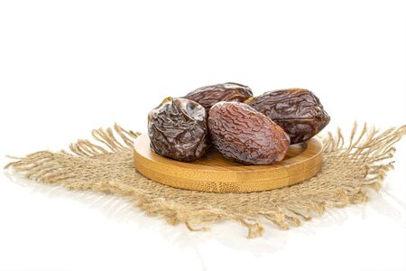 Group of four whole dried brown date fruit with jute fabric on round bamboo coaster isolated on white background