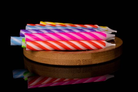 Lot of whole birthday cake candle heap on round bamboo coaster isolated on black glass 스톡 콘텐츠