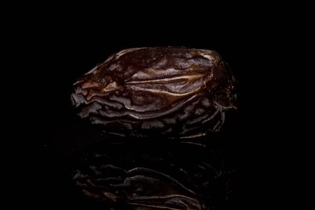 One whole dried brown date fruit isolated on black glass Reklamní fotografie - 136233765