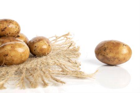 Lot of whole tiramisu brown almond nut with jute fabric isolated on white background