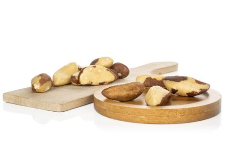 Lot of whole brazil brown nut on wooden cutting board on round bamboo coaster isolated on white background