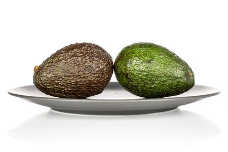 Group of two whole fresh green avocado on gray ceramic plate isolated on white background
