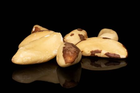 Group of seven whole brazil brown nut isolated on black glass