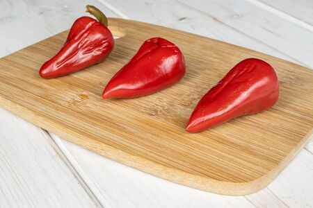 Group of three whole pickled red pepper on bamboo cutting board on white wood Reklamní fotografie - 136233781