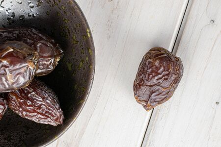 Group of five whole dried brown date fruit in glazed bowl flatlay on white wood Reklamní fotografie - 136233754