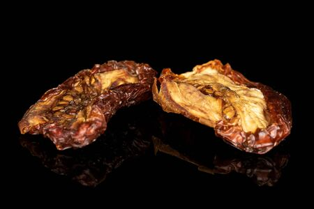 Group of two whole dried red tomato piece isolated on black glass Reklamní fotografie - 136233757