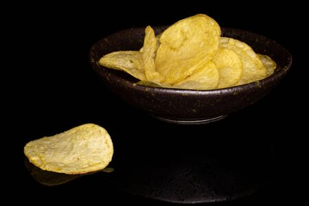 Lot of whole crisp potato chip in glazed bowl isolated on black glass