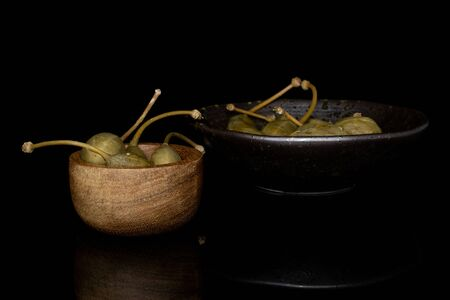 Lot of whole pickled green caper in bamboo bowl in glazed bowl isolated on black glass