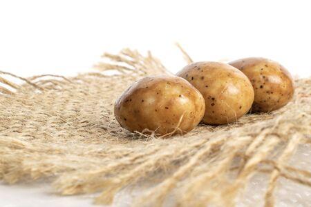Group of three whole tiramisu brown almond nut with jute fabric isolated on white background