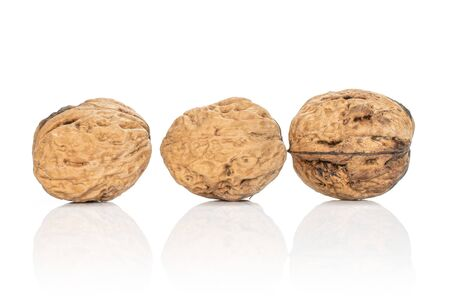 Group of three whole fresh brown walnut isolated on white background