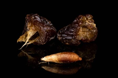 Group of two halves one piece of dried brown date fruit isolated on black glass