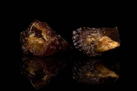 Group of two halves of dried brown date fruit isolated on black glass Reklamní fotografie - 136233299