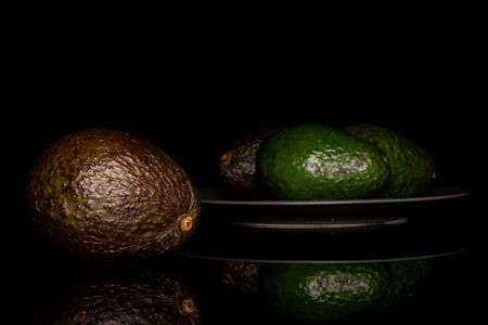 Group of four whole fresh green avocado on gray ceramic plate isolated on black glass