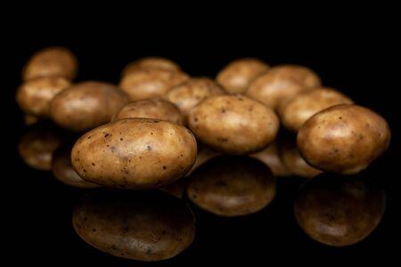 Lot of whole tiramisu brown almond nut isolated on black glass