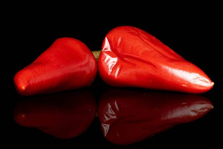 Group of two whole pickled red pepper isolated on black glass Reklamní fotografie - 136233718